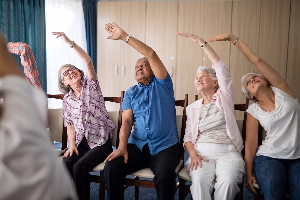 Smiling senior people stretching with female doctor
